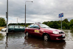 Cars trying to drive against flood on the street in Gdansk, Poland. Royalty Free Stock Photo