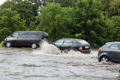 Cars trying to drive against flood on the street in Gdansk, Poland. Royalty Free Stock Photos