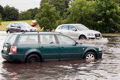 Cars trying to drive against flood on the street in Gdansk, Poland. Stock Photos