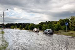 Cars trying to drive against flood on the street in Gdansk, Poland. Stock Photo
