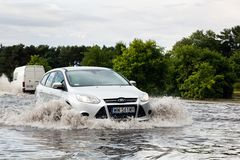 Cars trying to drive against flood on the street in Gdansk, Poland. Stock Image