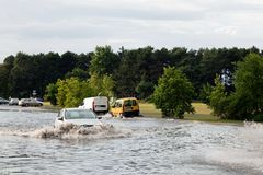 Cars trying to drive against flood on the street in Gdansk, Poland. Royalty Free Stock Images