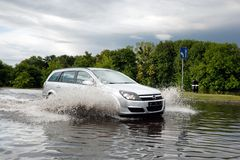 Cars trying to drive against flood on the street in Gdansk, Poland. Royalty Free Stock Image