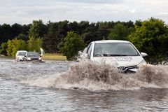 Cars trying to drive against flood on the street in Gdansk, Poland. Royalty Free Stock Photography