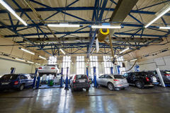 Cars in two-post lifters at workshop Royalty Free Stock Image