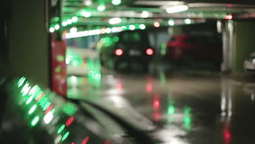 Cars in the underground parking. A lot of red and green lights on the blurred background stock video footage