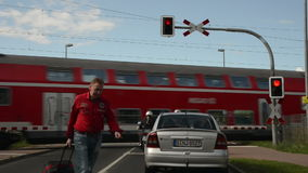 Cars waiting at a railroad crossing stock video footage