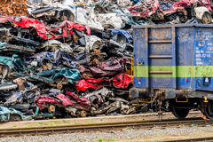 Cars were scrapped. Old cars were scrapped in a trash compactor. scrapping premium for car wrecks. scrap is loaded onto the train Stock Photos