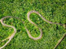 Cars on winding road trough the forest aerial view. Cars on winding road trough a forest aerial view from a drone royalty free stock photo