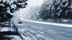 Cars on winter road with snow. Dangerous automobile traffic in bad weather. Royalty Free Stock Photos
