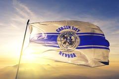 Carson- Cityhauptstadt von Nevada des Flaggentextilstoffgewebes Vereinigter Staaten, das auf den Spitzensonnenaufgangnebelnebel w lizenzfreies stockfoto