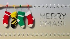 Cartão alegre do convite do texto do Xmas Peúgas de suspensão do Natal no fundo bege cinzento do inclinação Decoração colorida da Imagens de Stock Royalty Free