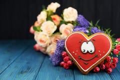 Cartão bonito com as cookies vermelhas de um smiley do coração no fundo fotos de stock