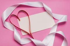 Cartão branco com com espaço da cópia, um coração de papel caseiro vermelho e uma fita branca em um fundo cor-de-rosa Símbolo do  imagem de stock royalty free