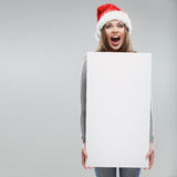 Cartão branco grande da posse da mulher do Natal Santa Hat Fotografia de Stock Royalty Free