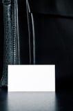 Cartão branco para escrever com o saco de couro preto na tabela Fotos de Stock Royalty Free