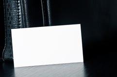 Cartão branco para escrever com o saco de couro preto na tabela Foto de Stock