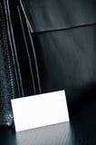 Cartão branco para escrever com o saco de couro preto na tabela Imagens de Stock Royalty Free