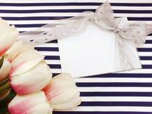 Cartão branco vazio com as flores artificiais bonitas e Empty tag para seu texto Foto de Stock