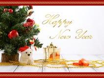 Cartão com árvore de Natal, caixa de presente do ouro, bolas, urso do brinquedo, doces e decorações na tabela branca do vintage r Foto de Stock