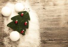 Cartão com as bolas de neve de uma árvore de Natal, das bolas do Natal e a neve no fundo de madeira Fotografia de Stock