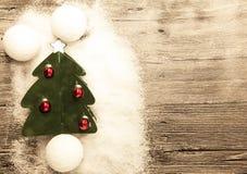 Cartão com as bolas de neve de uma árvore de Natal, das bolas do Natal e a neve no fundo de madeira Fotografia de Stock Royalty Free