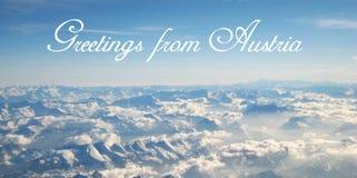 Cartão com belamente uma opinião do panorama de um voo sobre as nuvens e os cumes nevados em um dia ensolarado foto de stock
