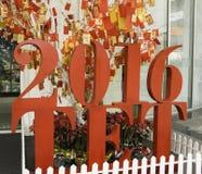 Cartão com a imagem de um macaco que pendura em uma árvore de Natal TET que vem logo Ano novo chinês Fotografia de Stock