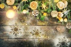 Cartão com presentes, vela do Natal, cones, varas de canela, laranja seca, árvore verde sobre o fundo de madeira escuro velho Foto de Stock Royalty Free