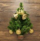 Cartão com uma árvore de Natal, as bolas do Natal, os sinos, e a estrela no fundo de madeira Imagens de Stock