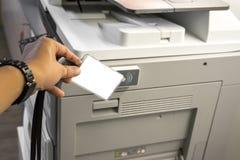 Cartão da posse da mão do homem para que o cartão chave de varredura alcance o conceito de sistema da segurança da fotocopiadora Imagem de Stock Royalty Free