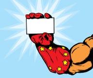 Cartão da terra arrendada da mão do super-herói Fotografia de Stock