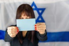 Cart?o da terra arrendada da mulher, c?dula vazia, papel de vota??o Front Of Face no fundo israelita da bandeira Espa?o para o te imagem de stock