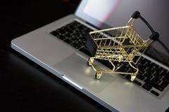 Cartão de banco em linha da compra próximo um portátil e um mini carrinho de compras Fotografia de Stock