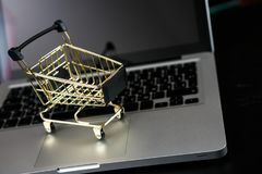 Cartão de banco em linha da compra próximo um portátil e um mini carrinho de compras Fotos de Stock