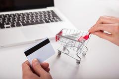 Cartão de banco próximo um portátil e um mini carrinho de compras fotos de stock