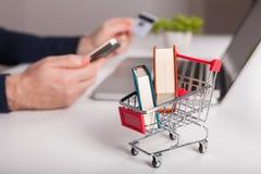 Cartão de banco próximo um portátil e um mini carrinho de compras no backg branco imagens de stock