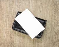 Cartão de couro preto do titular do cartão e o branco no fundo de madeira A vista superior da carteira de couro para mantém seu d imagem de stock royalty free
