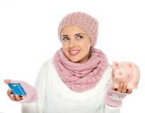 Cartão de crédito confuso da terra arrendada da mulher e banco piggy Fotos de Stock