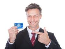 Cartão de crédito da terra arrendada do homem de negócios fotos de stock royalty free