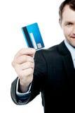 Cartão de crédito de sorriso da terra arrendada do homem de negócios foto de stock