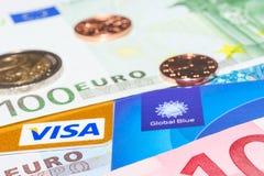 Cartão de crédito do visto e isento de impostos azul global contra o dinheiro do dinheiro Imagem de Stock Royalty Free