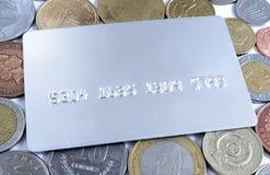 Cartão de crédito sobre moedas Imagens de Stock