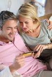 Cartão de crédito uding dos pares maduros para a compra do Internet Foto de Stock