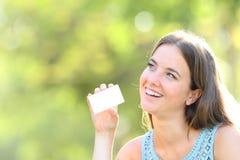Cartão de crédito vazio feliz da exibição da mulher que olha o lado foto de stock