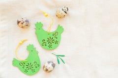 Cartão de easter feliz ainda vida com ovos de codorniz e a galinha de madeira decorativa nas toalhas de mesa de linho Feriado da  fotos de stock