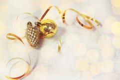 Cartão de Natal bola dourada das decorações do Natal, pinecone, fita dourada em um fundo branco com neve e luzes suaves fotografia de stock