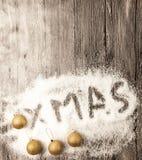 Cartão de Natal com as bolas douradas do xmas da inscrição na neve em um fundo de madeira Imagens de Stock
