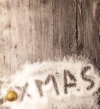 Cartão de Natal com as bolas douradas do xmas da inscrição na neve em um fundo de madeira Imagem de Stock Royalty Free
