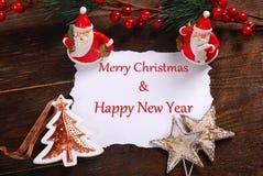 Cartão de Natal com dois cláusulas e cumprimentos de Santa imagens de stock